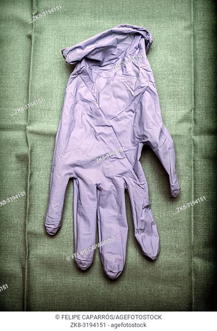 Glove of latex blue on green cloth in an operating theater, conceptual image