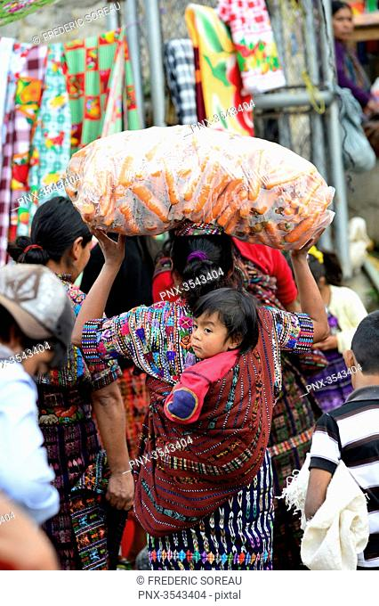 Guatemalan woman carrying child in sling on her back, lake of Atitlan, Solola market, Guatemala, Central America