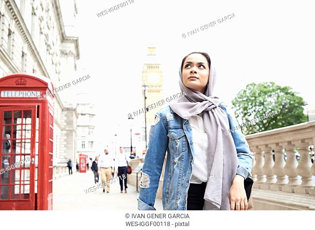 UK, England, London, young woman wearing hijab walking in the city
