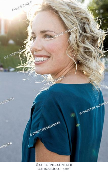Happy mid adult woman in sunlit park