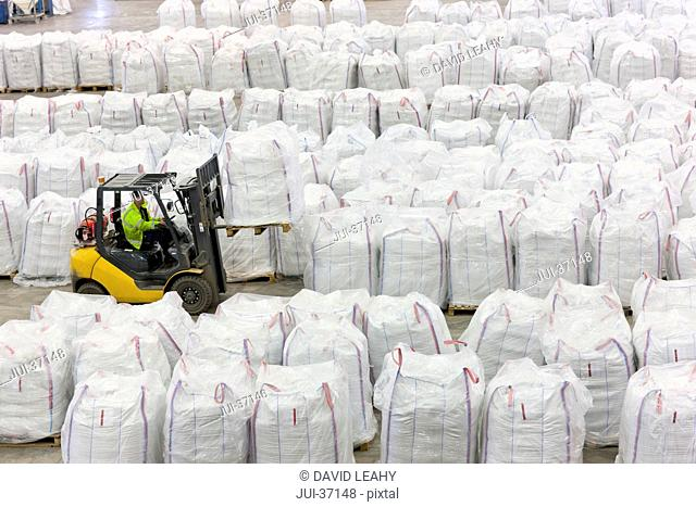 Forklift operator lifting large bag of recycled plastic pellets in warehouse