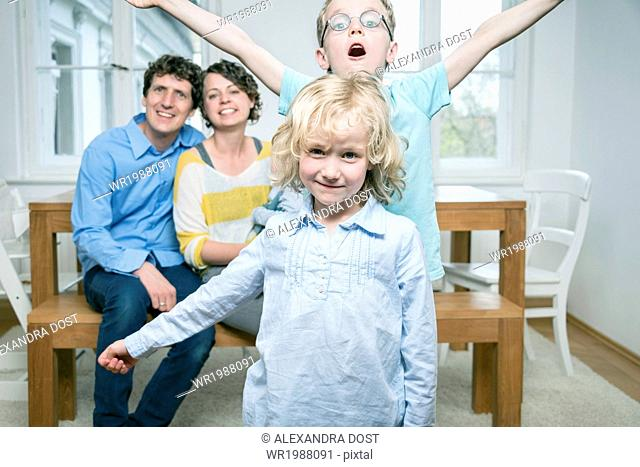 Family with three children in living room