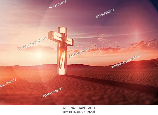 Person in suspended animation inside crucifix in desert