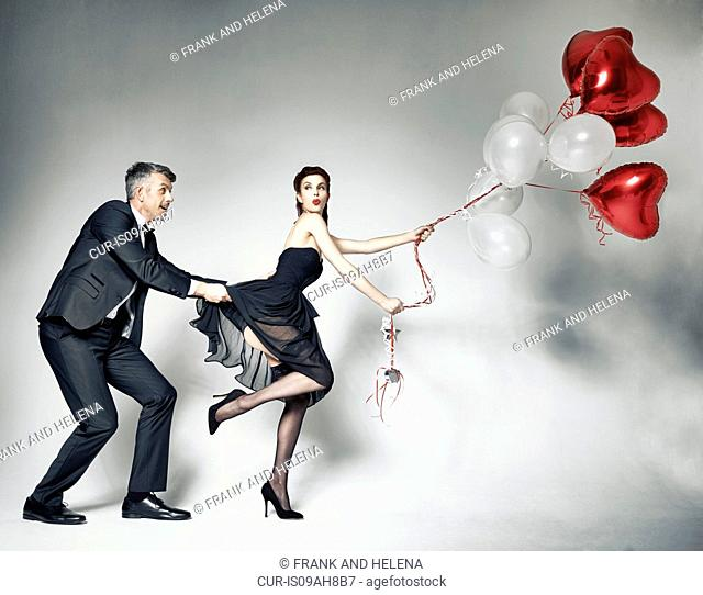 Man pulling dress of woman with heart-shaped balloons