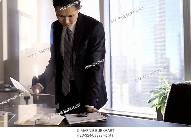Male lawyer reviewing paperwork and checking cell phone in office