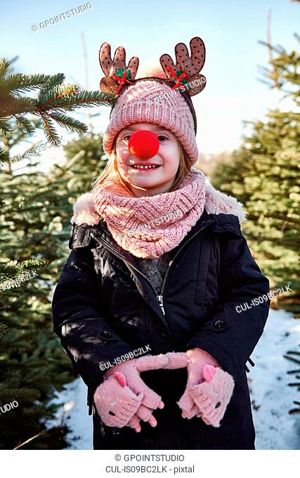 Girl in christmas tree forest with red nose, portrait