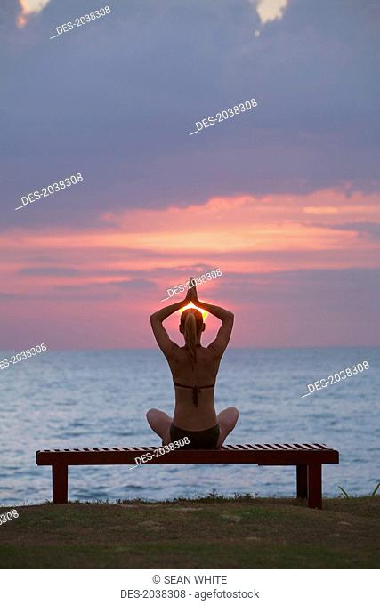 A Woman Tourist Does Yoga And Stretching At Sunset On The Beach Of A Tropical Island, Koh Lanta Thailand