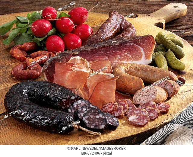 Cold platter, wooden tray with Tyrolean ham, farmer's blood sausage, liver sausage, smoked kaminwurz, radishes and gherkins