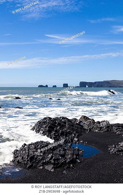 View of basalt sea stacks from the black sand beach at Reynisfjara in Iceland