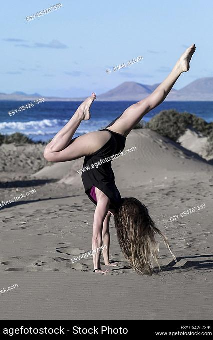 Side view of athletic woman showing asana in handstand while practicing on sunny beach