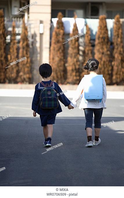 Two kids walking on road