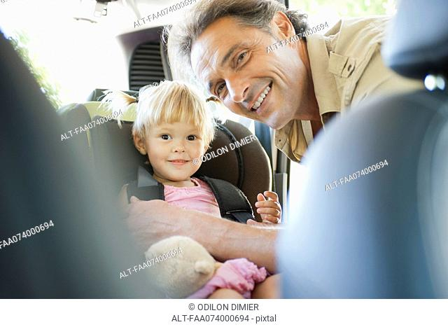 Father fastening little girl into car seat, both smiling at camera