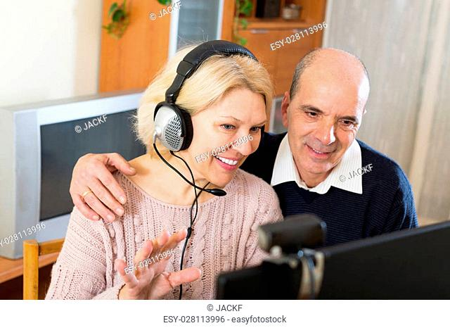 Positive european pensioneers in headphones are sitting in front of pc and making a video call to their childrens in USA