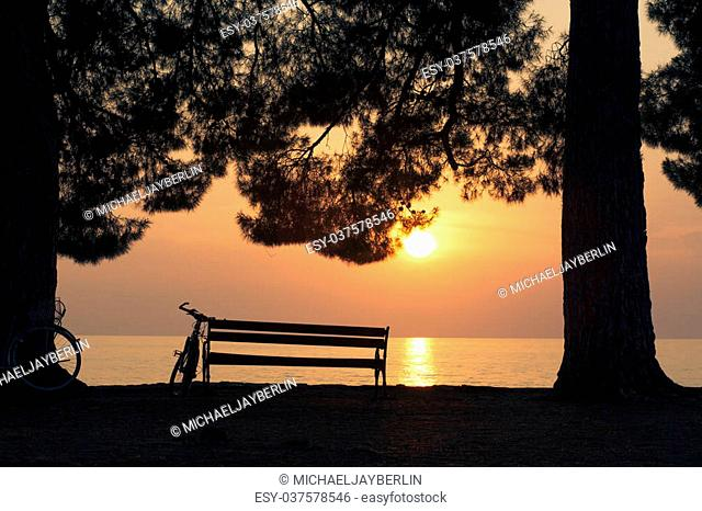 Nobody sitting on an bench at the Mediterrean Sea in Croatia at sunset but someone's bike leaning on the bench