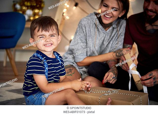 Portrait of boy opening Christmas present at home