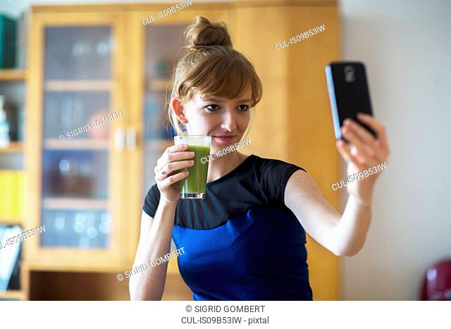 Young woman holding smoothie, taking selfie with smartphone