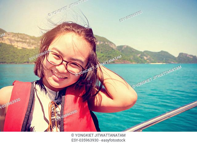 Vintage style young woman with eyeglasses smiling happily on the boat while cruising the natural of the sea and island in summer at Mu Ko Ang Thong National...
