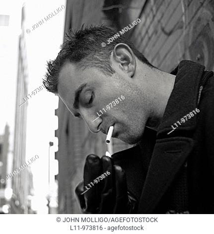 Close-up of man in alley, lighting a cigarette