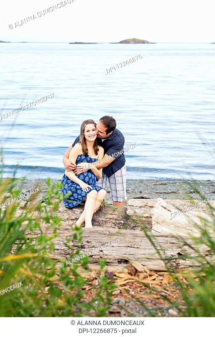 A young couple poses for pregancy portraits on a beach at the ocean, expecting their first child for their family; Nanaimo, British Columbia, Canada