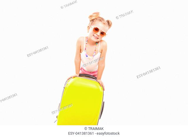 Isolated on white, attractive young caucasian blonde girl in white shirt, pink shorts, sunglasses and sandals stand near the yellow suicase