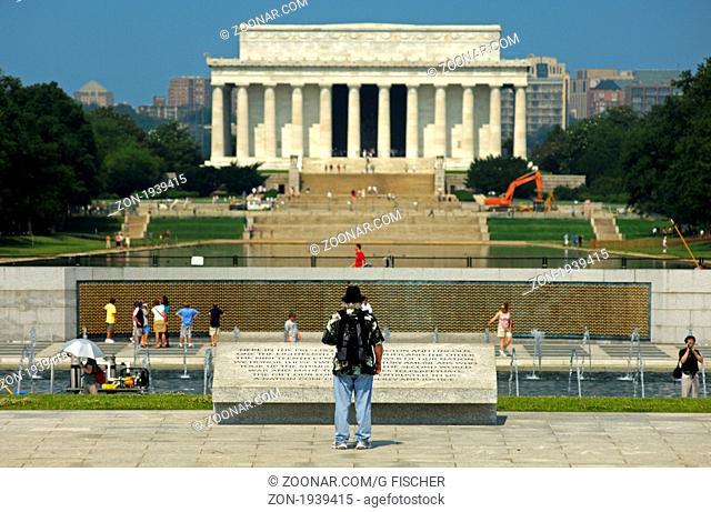 Besucher liest die Inschrift am Denkmal für den Zweiten Weltkrieg, World War II Memorial, das Lincoln Memorial hinten, Washington D.C