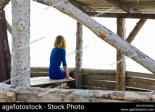 A girl sits on a table in a gazebo from a log house