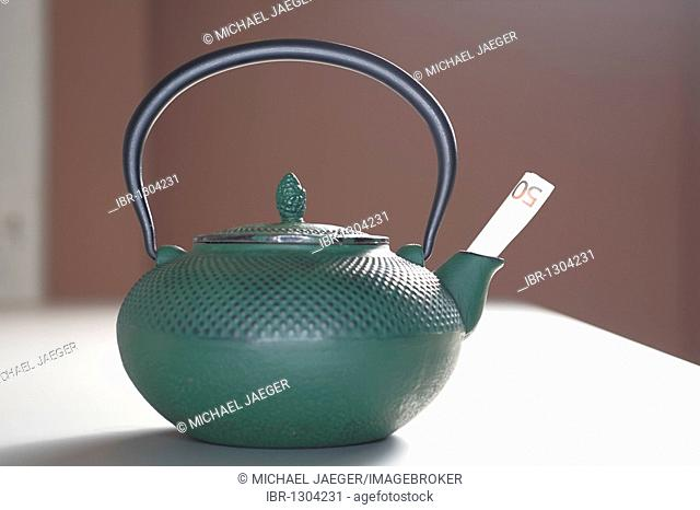 Cast iron teapot with a banknote in the pouring spout