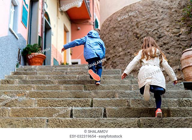 Kids running upstairs at street of colorful Manarola village, Cinque Terre, Italy