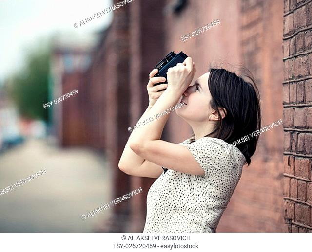 Pretty young woman taking photo outdoors. Girl holding vintage camera and taking photographs. Retro style photo. Selective focus on woman