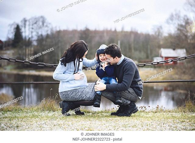 Small boy with father and pregnant mother during walk