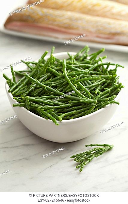 Fresh raw green samphire in a bowl with fresh fish in the background