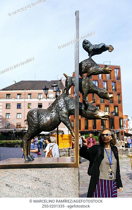 Tourists touching sculpture of the Town Musicians of Bremen. Riga, Latvia, Baltic states, Europe