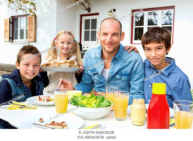 Portrait of father and three children at garden barbecue table
