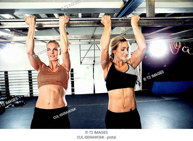 Two women training on exercise bar in gym