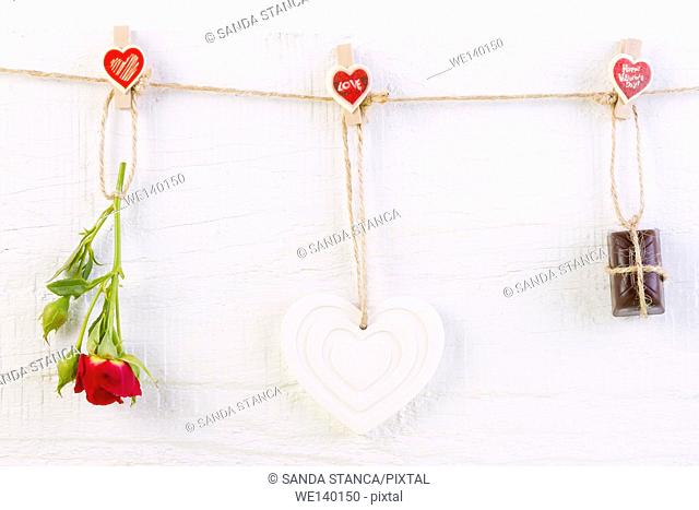 Red rose with white shape heart and chocolate on white wooden background