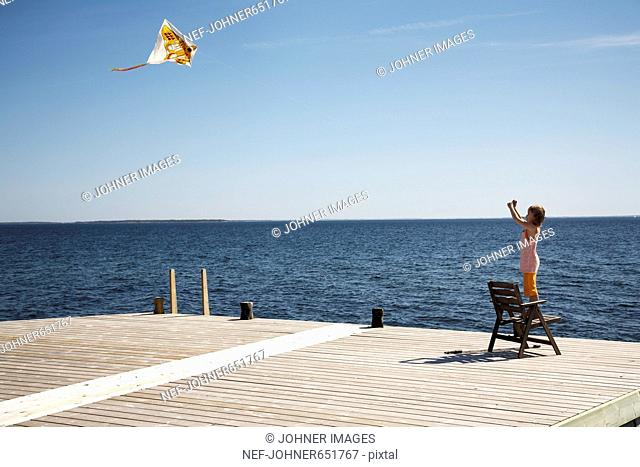 A girl on a jetty holding a kite, Sweden