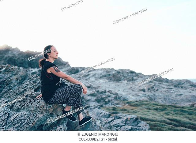 Side view of woman sitting on rocks looking away, Stintino, Sassari, Italy