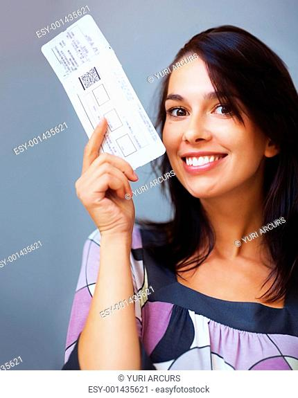 Closeup portrait of beautiful woman holding boarding pass on colored background