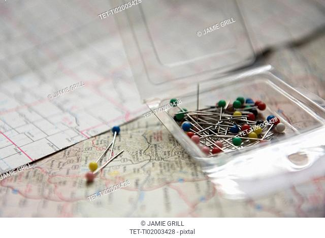 Pins in box lying on map