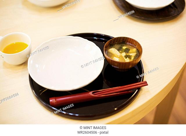 Family home. A table place set for a meal. Mat, bowl and chopsticks