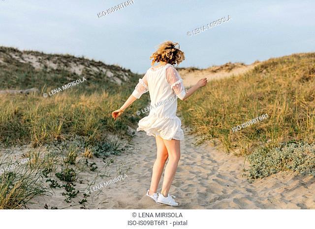 Young woman in white dress dancing on coastal dunes, Menemsha, Martha's Vineyard, Massachusetts, USA