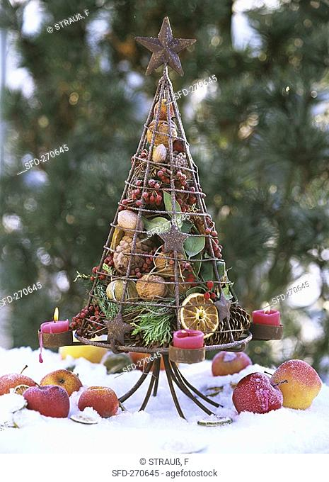 Iron tree filled with fir cones, candles, fruit, berries