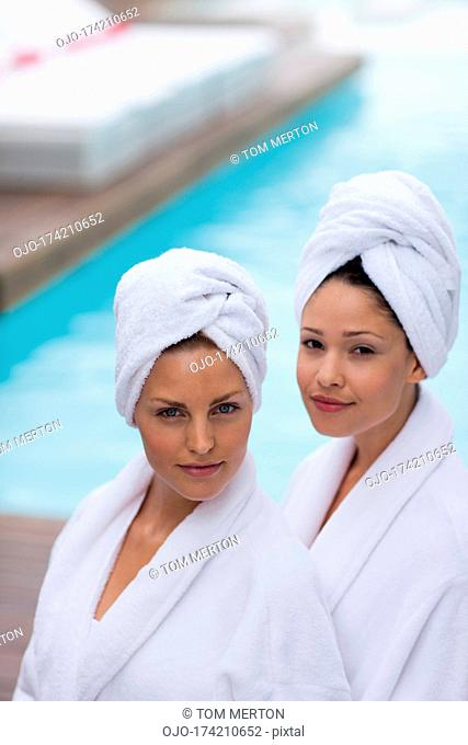 Women with hair wrapped in towels at poolside
