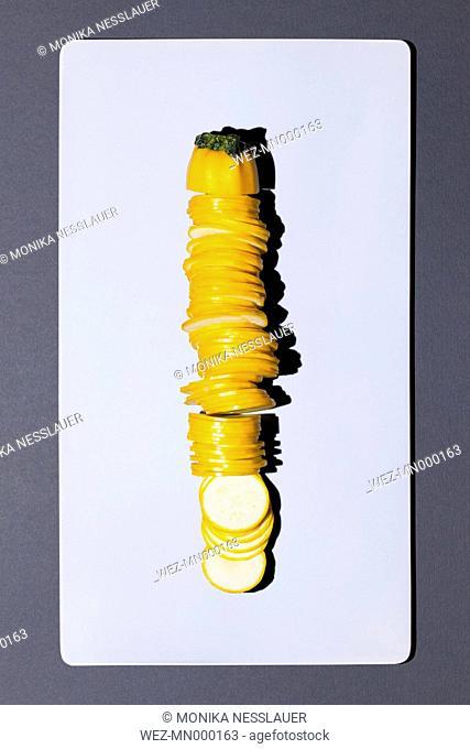 Sliced yellow zucchini on white board