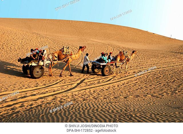 Tourists on camel cart safari , Khuhri , Jaisalmer , Rajasthan , India