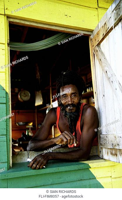 Man in the window of his rum shop, Black Creek, Jamaica