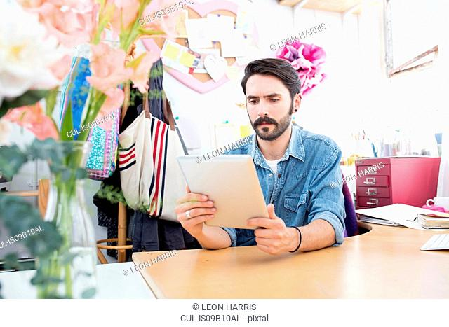 Young male designer reading digital tablet in printing press studio
