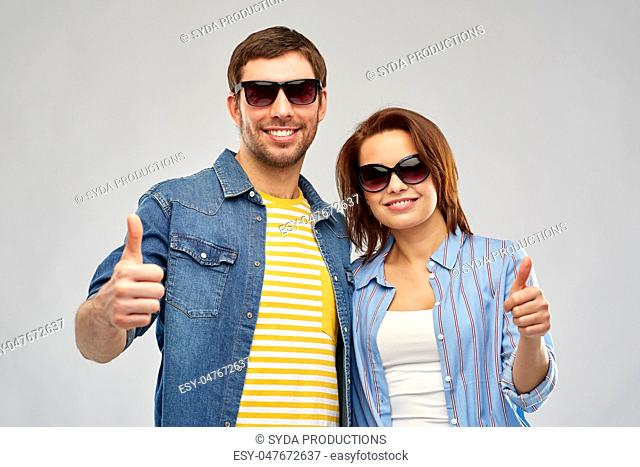 happy couple in sunglasses showing thumbs up