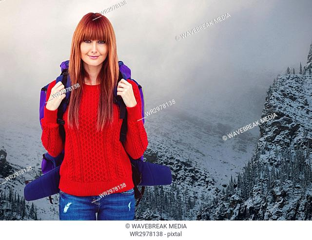 Millennial backpacker smiling against snowy mountains