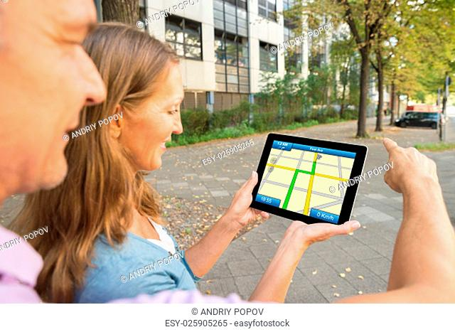 Happy Couple Looking At Gps Map On Digital Tablet